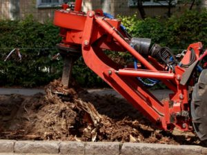 A tree stump being removed with a red tree stump removal machine